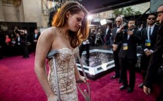 Na foto da Getty Images, Kristen Stewart chega ao Oscar 2012/2013 de muletas: a atriz teria cortado o pé dias antes, pisando em um caco de vidro